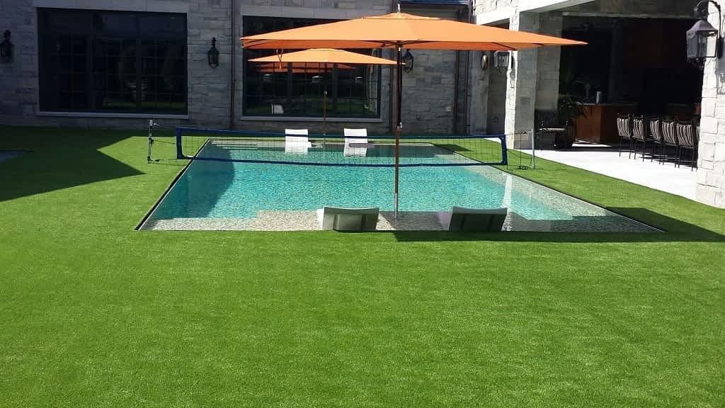 Quais são as vantagens de usar grama sintética ao redor da piscina em sua casa?